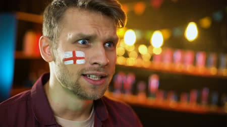 gesticulando : Satisfied english football team supporter with flag painted on cheek cheering