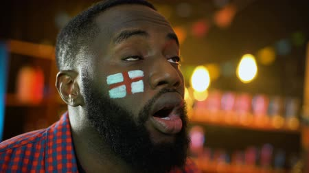 gesticulando : Black male with english flag painted on cheek disappointed football team failure
