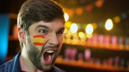 gesticulando : Spanish football fan with flag on cheek cheering for team winning tournament