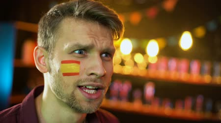 gesticulando : Happy spanish football supporter with flag on cheek shouting, team scoring goal