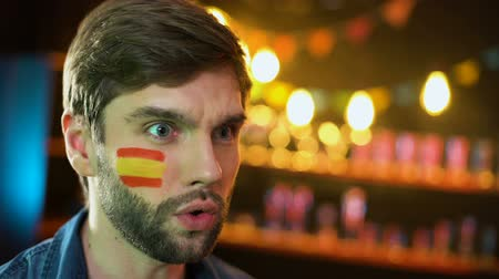 判決 : Nervous fan with spanish flag on cheek making facepalm dissatisfied with match