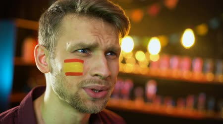 gesticulando : Anxious caucasian fan with spanish flag on cheek unhappy with match result Vídeos