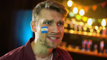 yanak : Football fan with argentinian flag on cheek making facepalm, unhappy with loss Stok Video