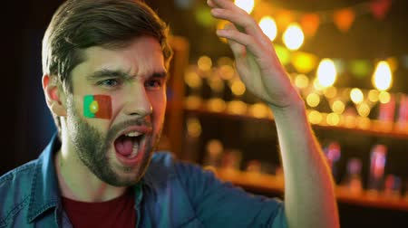 facepalm : Nervous portuguese football fan with flag on cheek making facepalm, team losing
