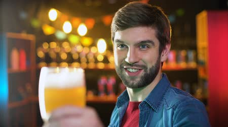pivovar : Handsome bearded male clinking beer glasses with friend, weekend results in pub