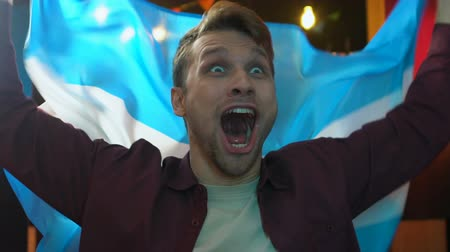 rúgbi : Extremely cheerful fan waving Argentina flag in bar rejoicing national team goal Vídeos