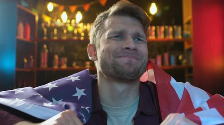 porażka : Sad male fan waving flag of USA in bar, displeased about national team defeat