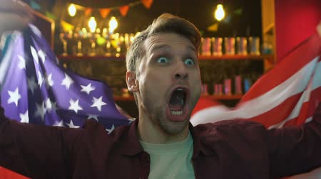 regozijo : Extremely glad male fan waving flag of USA, rejoicing national team victory Stock Footage