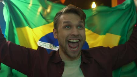 brazil : Excited male fan waving Brazilian flag in bar, rejoicing sports team victory Stock mozgókép