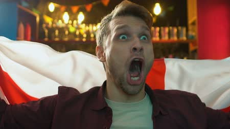 regozijo : Emotional male fan waving flag of England in pub rejoicing national team victory