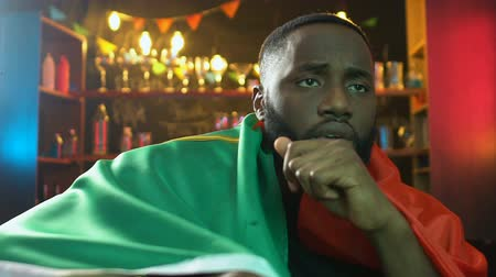 penas : Sad black fan holding flag of Portugal in bar, upset about sports team defeat
