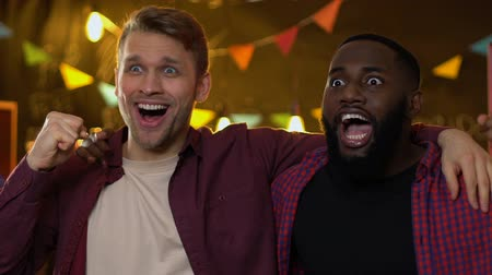 league : Smiling multi ethnic male fans rejoicing national sports team victory in bar. Stock Footage