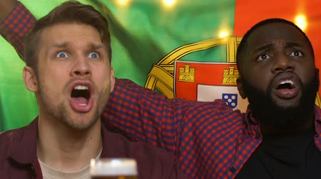 penas : Friends in bar holding Portuguese flag, upset about national football team loss Stock Footage