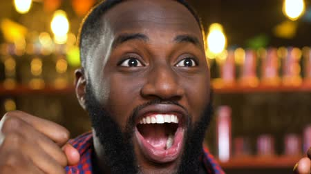 gritante : African-American man in pub extremely happy about favorite sports team victory