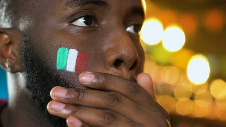 expressing negativity : Black male fan with Italian flag on cheek upset about favorite team losing game