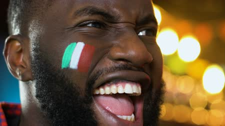 marş : Afro-American sports fan rejoicing favorite team victory, Italian flag on cheek