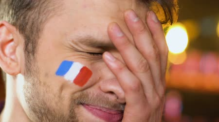 french team : Male fan with French flag on cheek upset about favorite sports team losing game Stock Footage