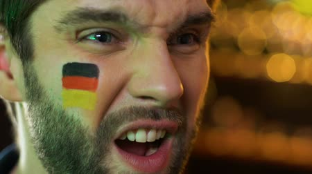 facepalm : Male fan with German flag on cheek upset about favorite sports team losing game