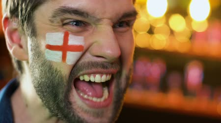 marş : English football fan extremely happy about favorite team victory, flag on cheek Stok Video