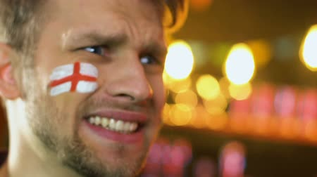 penas : English football fan with flag on cheek upset about favorite team losing match