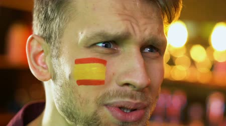 trest : Male fan displeased with national football team loss, Spanish flag on cheek
