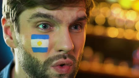 facepalm : Argentinian fan making facepalm gesture, upset about favorite team losing game Stock Footage
