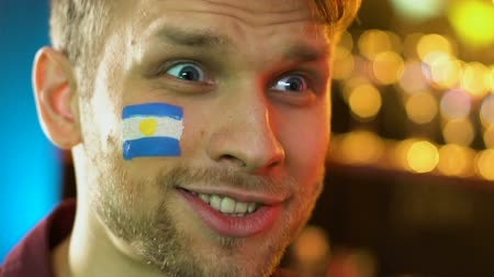 фэн : Argentinian football fan happy about favorite team victory painted flag on cheek