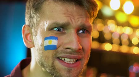 facepalm : Argentinian male fan displeased with national football team loss, flag on cheek