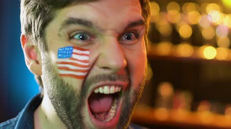 marş : American football fan with flag on cheek rejoicing favorite team victory, league