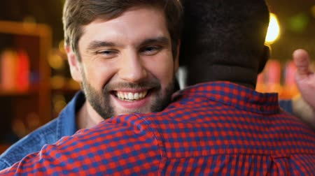 atender : Two multiethnic men hugging in bar, unexpected old friends meeting, relax