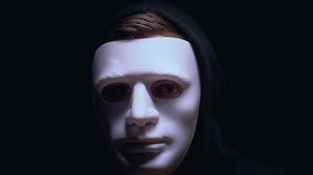 maniac : Man hiding wounded face under mask, isolated on black background, criminal. Stock Footage