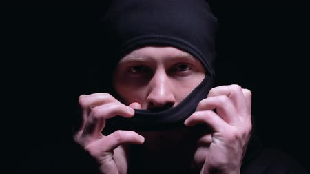 stalker : Serious man wearing balaclava preparing for terrorism action, black background Stock Footage