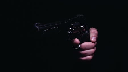 roubo : Hand of bandit aiming gun at victim, isolated on black background, crime scene Stock Footage