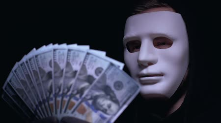 serial : Smiling boss of mafia in mask holding bunch of dollars, robbery, dark background Stock Footage