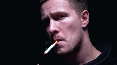 deguisement : Confident gangster lighting cigarette and looking at camera, dark background Vidéos Libres De Droits