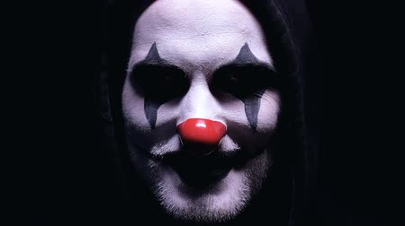 psycho : Creepy clown smiling into camera isolated on black background, horror, close-up Stock Footage