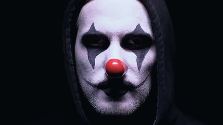 ijesztő : Evil clown smiling to camera against dark background, dangerous maniac in mask Stock mozgókép
