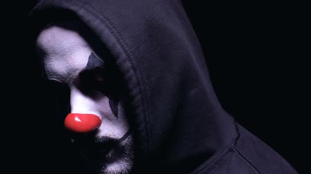 psycho : Clown with crazy smile turning to camera against dark background, nightmare