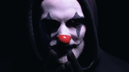 жертва : Crazy maniac with clown face mask thinking about next victim, planning murder