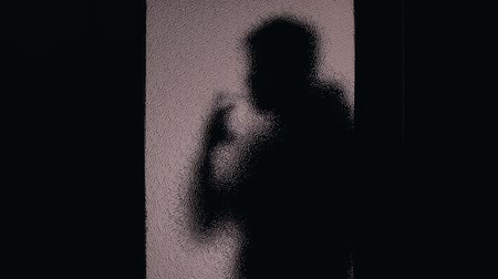 harmful habit : Silhouette of man smoking behind closed door, work break, nicotine addiction