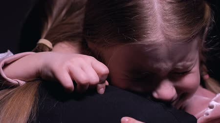 нежный : Crying little girl hugging mother and looking at camera, suffering from bullying