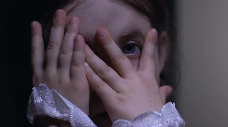 imaginário : Cute little girl peeking through fingers, scared of forbidden adult content Stock Footage