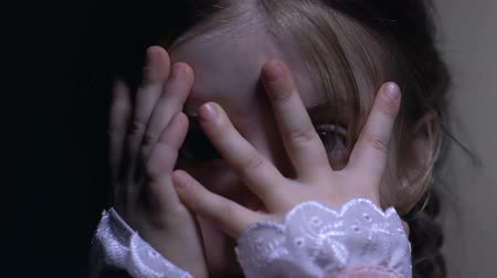 fobi : Scared cute little girl covering face with hands, danger or domestic violence Stok Video