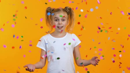 regozijo : Cute girl is surprised seeing falling from sky confetti, celebration, childhood