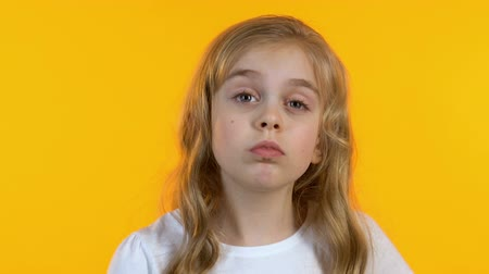 attitude : Cute little girl scratching head, trying to remember info, isolated background Stock Footage