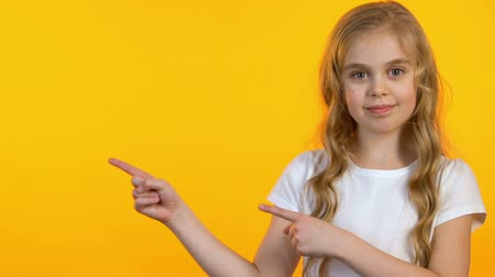 aanprijzen : Smiling girl pointing fingers at empty space on yellow background, template