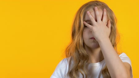 embarrassed : Sad schoolgirl making facepalm, tired of hard school lessons, vitamin deficiency Stock Footage