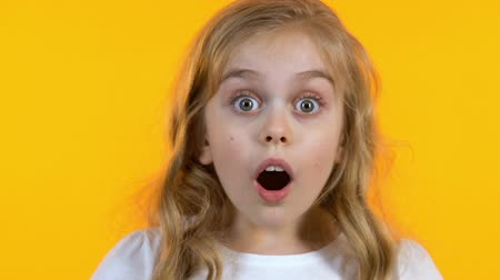 údiv : Blonde girl looking extremely shocked hearing news, isolated yellow background Dostupné videozáznamy