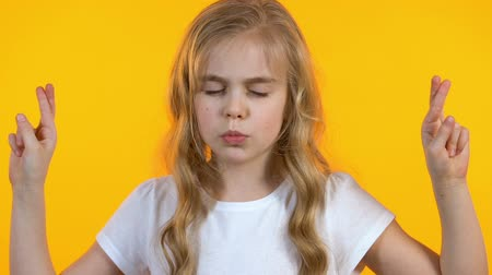 pleading : Little girl crossing fingers and making wish, strong desire, childish naivety Stock Footage