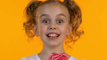 pigtail : Extremely happy little girl enjoying taste of heart-shaped lollipop, close-up